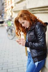 frau ist in der stadt unterwegs und schaut auf ihr mobiltelefon