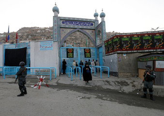 Afghan policemen stand guard outside the Sakhi Shrine after a overnight attack in Kabul, Afghanistan