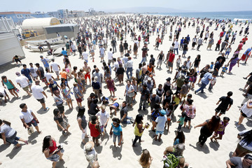 Hundreds of people search for hidden money placed in the sand by an anonymous internet benefactor in Hermosa Beach