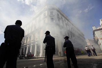 Smoke comes out of a school after it caught fire as police cordon off a street in Havana
