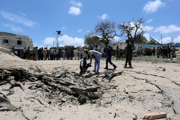 Somali security forces assess the scene of a car bomb outside the president's palace in the Somali capital of Mogadishu