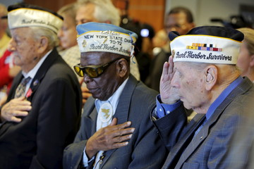 Pearl Harbor survivors Armando Gallela, Clark Simmons, and Aaron Chabin salute during a singing of the Star Spangled Banner during a ceremony on the Intrepid Sea, Air, & Space Museum in New York Harbor