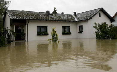 A house is partially submerged in a flooded street in the village of Sarling