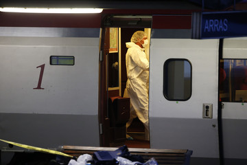 French investigating police in protective clothing collect clues inside the Thalys high-speed train were shots were fired in Arras