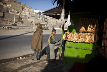 Afghan man waits for bus in front of a bakery in Kabul