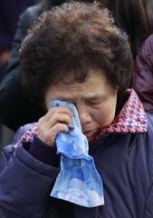 A Christian wipes her eye as she prays for North Koreans during a prayer for human rights at a city hall plaza in Seoul