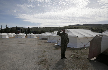 A Greek soldier salutes as he stands next to tents at a newly operational relocation camp for refugees in Schisto, near Athens