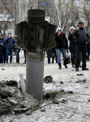 People take pictures of the remains of a rocket shell on a street in the town of Kramatorsk