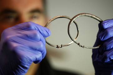 Silver arm-rings are held by metal-detectorist, James Mather, who discovered a Viking Hoard, which also included silver ingots and rare coins of King Alfred of Wessex and King Ceolwulf II of Mercia, at the British Museum London