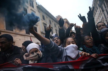 A girl holds up a smoke grenade as protesters and squatters demand for housing rights in downtown Rome