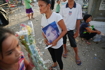 Mother of Angelo Lafuente, whose body was found by a filthy river that feeds into the Manila bay, holds his picture as she visits his grave on the All Saints Day in Manila