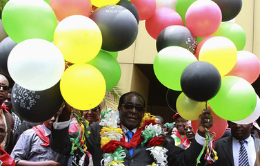 Zimbabwe's President Robert Mugabe holds onto 87 balloons as he celebrates his birthday at a rally organised by his ZANU-PF party in Harare