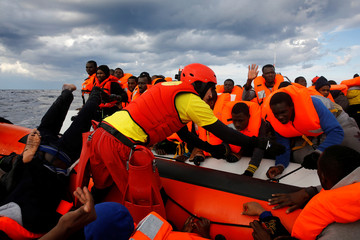 Panicking migrants try to reach a rescue craft from their overcrowded raft in Mediterranean Sea