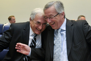 IMF Managing Director Strauss-Kahn smiles with Luxembourg's PM Juncker at the start of an Euro zone finance ministers meeting in Luxembourg