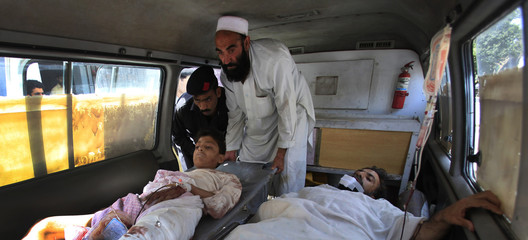 Men who were injured by a suicide bomb attack in Kohat, are helped out of an ambulance after arriving to the Lady Reading hospital for treatment in Peshawar