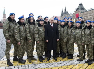 Russian President Putin poses for photo with members of youth military patriotic club during flower-laying ceremony in Red Square in Moscow