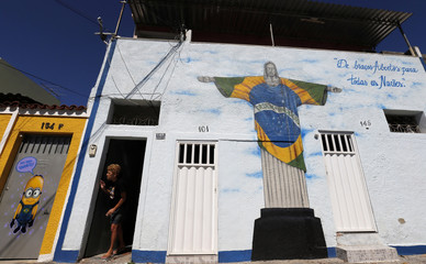 A woman looks out from her house next to graffiti depicting the iconic Christ the Redeemer with the Brazilian flag design painted in reference to the 2014 World Cup in Rio de Janeiro