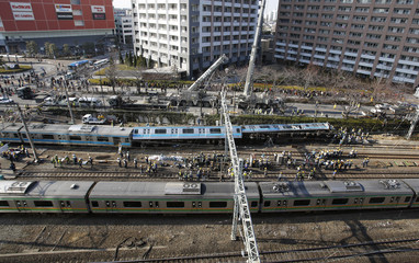 Officials inspect a train collided with a maintenance car near Kawasaki Station in Kawasaki