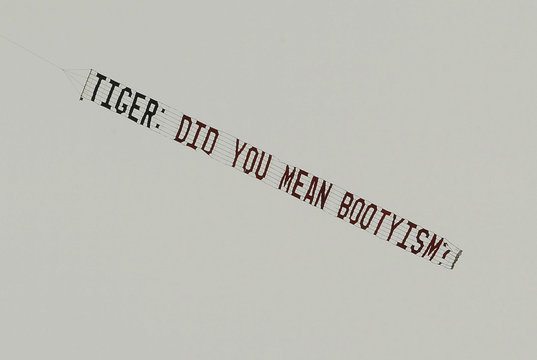 A banner pulled by a small airplane flies nearby during first round play with Tiger Woods on the first tee for his start in the 2010 Masters golf tournament in Augusta