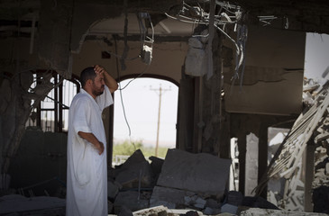 A man stands in a house Libyan officials say was bombed by NATO forces in Majar, a village south of Zlitan