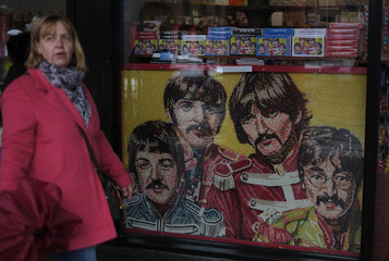 A woman walks past a picture of the Beatles made from Jelly Beans in the window of a sweet shop in Liverpool northern England