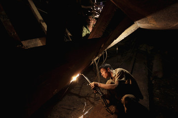 Workers weld at a ship-building yard next to Buriganga River in Dhaka