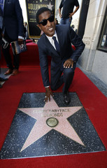 Singer and songwriter Edmonds poses on his star after it was unveiled on the Walk of Fame in Hollywood