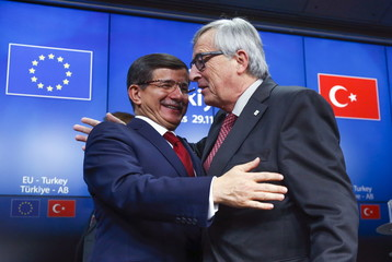 Turkish Prime Minister Ahmet Davutoglu and European Commission President Jean Claude Juncker greet each other after a news conference following a EU-Turkey summit in Brussels