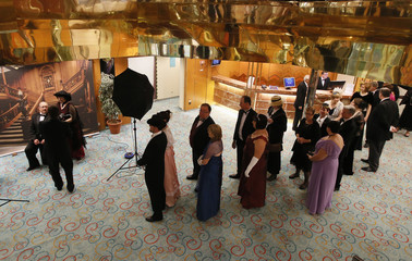 Guests in formal dress queue to have their pictures taken on board the Titanic Memorial Cruise in the mid-Atlantic Ocean