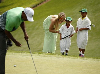 Woods of the U.S. sets up his putt on the first green as his girlfriend Vonn and his two children Charlie and Sam watch during the par 3 event held ahead of the 2015 Masters at Augusta National Golf Course in Augusta