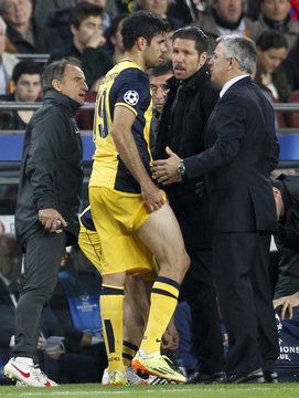 Atletico Madrid's Costa  talks with his coach Simeone and team's doctor after injuring his right leg during their Champions League quarter-final first leg soccer match against Barcelona in Barcelona