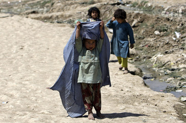 An internally displaced Afghan girl raises a burqa she is wearing at a refugee camp in Kabul