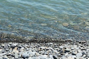 каменистый  пляж из серых камней уходящий в море