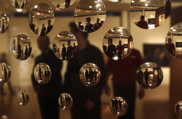 "People are seen through the acrylic bubbles of the art piece ""Concave Circles"" by Argentine artist Polesello at the Museum of Modern Art in Mexico City"