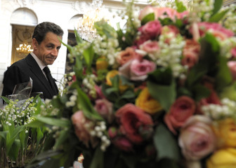 France's President Sarkozy looks at flowers during the annual Lily of the Valley ceremony at the Elysee Palace in Paris