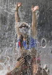 A girl plays under the waterfall at the the fun bath in Endenich