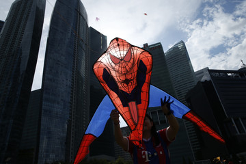 A woman flies a kite depicting comic book superhero Spider-Man kite during the annual Singapore Kite Festival at the central business district area of Marina Bay in Singapore