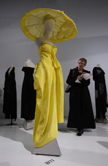 A visitor looks at a yellow strapless silk dress and oversized coolie hat covered with draped silk designed by Yohji Yamamoto at the V&A in London