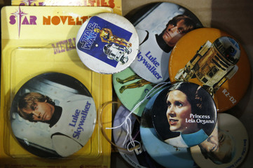 Vintage Star Wars themed badges sit in a tray ahead of a auction of Star Wars and film related toys at the Vectis auction house in Stockton-on-Tees