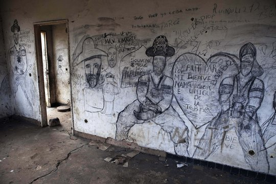 War-time graffiti adorns the walls of a guest room in a destroyed luxury resort in eastern Congo
