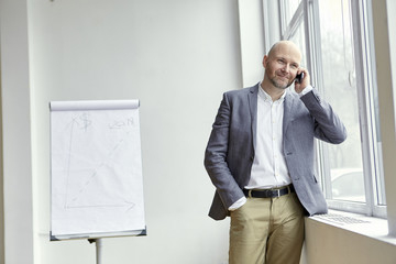 Bald Man Standing and Smiling During a Nice Phone Call