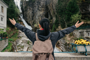 Austria. Bad Gastein. Girl traveler with a backpack near the Alpine falls