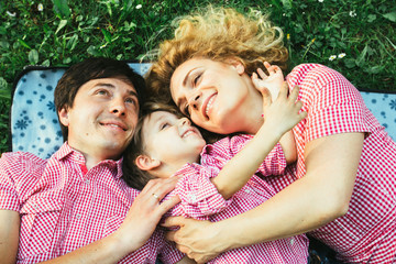 Unique perspective of happy european family smiling while lying down on the green grass in the park
