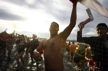 A man runs into the English Bay during the annual New Year's Day Polar Bear Swim in Vancouver