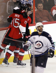Senators' Smith celebrates captain Alfredsson's goal as Jets' Oduya skates to the bench during the third period of their NHL hockey game in Ottawa