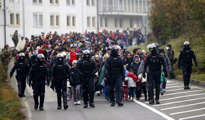 Slovenian police escort migrants walking towards the Austrian border near the village of Sentilj, Slovenia