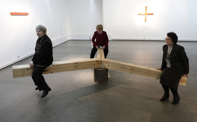 "Women try an installation called ""Triple balance"" by French artist Hybert at his exhibition at the Museum of modern art in Russia's Siberian city of Krasnoyarsk"