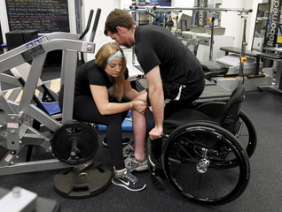 Kristen Johnson, a spinal cord injury recovery specialist, helps paraplegic Adam Fritz into position to workout at the Project Walk facility in Claremont, California