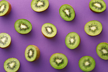 Kiwi slices pattern on a purple background. Repetition concept. Top view. Flat lay
