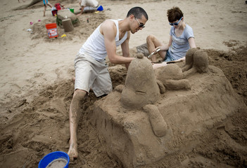 Sand sculptors Sand and Randell work on a sand sculpture of the cartoon character Snoopy during the annual Coney Island Sand Sculpting Contest in New York